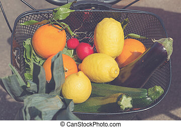 Bicycle basket filled with fresh fruits and vegetables from marketplace.