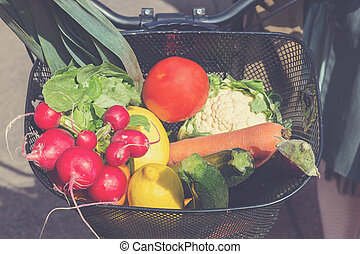Bicycle basket filled with fresh vegetables from marketplace.