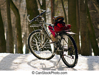 Bicycle being on a snow in a sunny day