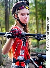 Girl rides bicycle on green grass in park outdoor. - Bicycle...