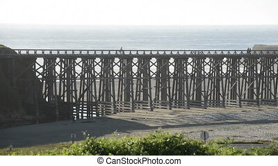 Bicycle crosses a foot bridge by the ocean shore, time lapse