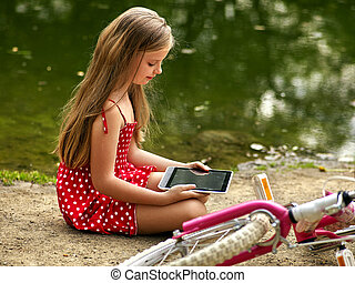 Bicycle girl into park. Children watch tablet pc.