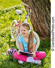 Bicycle girl wearing helmet watching at tablet pc in cycling.