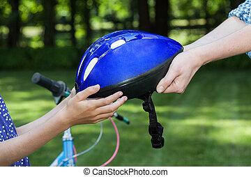 Bicycle helmet - Close up of bicycle helmet held by two...
