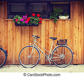 bicycle in backyard with geraniums - Bicycle parked near a...