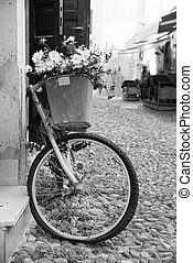 a view of a pedestrian street in the old town of Alghero, Sardinia, Italy, with an old bicycle parked in a wall in the foreground, in black and white