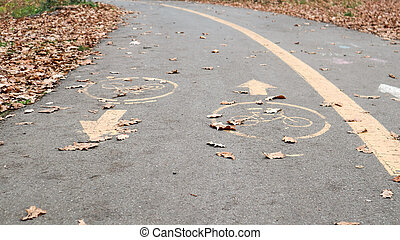 Bicycle lane on the side of a city road in the fall. Road marking in the form of two oncoming arrows on an asphalt path in the autumn park. Fallen leaves in the forest. Fall season concept