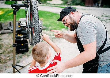 Bicycle mechanic show bike to young boy