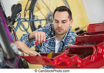 Bicycle mechanic taking screwdriver from toolbox
