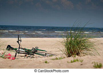 bicycle on beach sand with sea in background