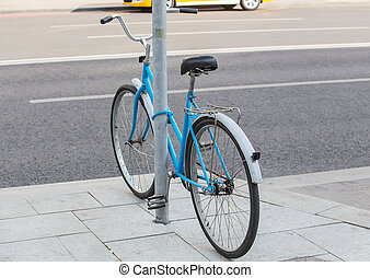 bicycle parked and fastened to pole
