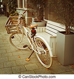 Bicycle parked near bench on the street
