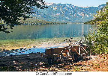 Bicycle parked near the wooden bench on the shore of lake Bohinj
