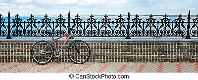 Bicycle parked on the bank of the river. Concept of eco friendly transport and healthy active lifestyle. Banner for website