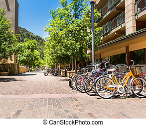 Bicycle parking in touristic town. Mountain and blue sky on...