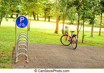 Bicycle parking sign on slope area with red bicycle.