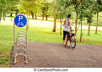 Bicycle parking sign on slope area with woman and red bicycle.