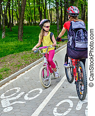 Bicycle path for child girls wearing helmet with rucksack ...