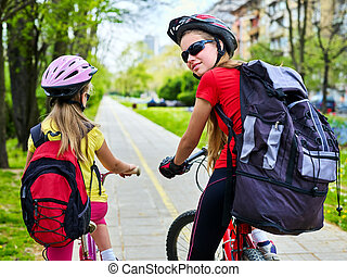 Bicycle path with children. Girls wearing helmet with ...
