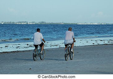 Bicycle Riding - Two people riding bikes on the beach, Ft....