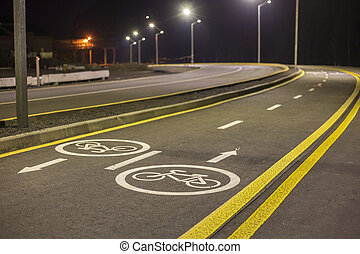 Bicycle Road Markings and Signs. Illuminated bicycle lane travel lane reserved for bicyclists with pavement markings with arrows that direct bicyclists in the direction of travel at night.