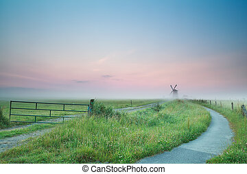 bicycle road to windmill in sunrise fog