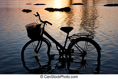 bicycle silhouette standing in the water at sunset.