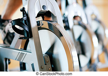 Bicycle Spinning in gym - Three people spinning in the gym,...