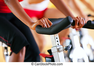 Three people spinning in the gym, exercising for their legs and cardio training
