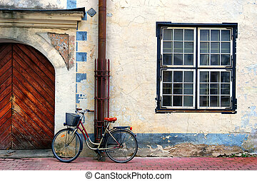 Bicycle stands at the gate in an old house with a square window