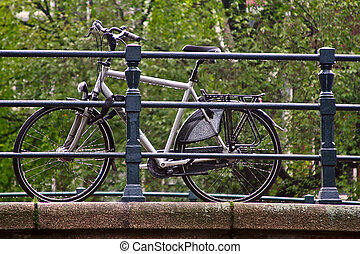 bicycle in the rain on the bridge via canal in Amsterdam,...