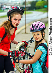Bicycle tire pumping and repair by child bicyclist on road...