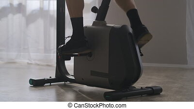 bicycle training at home, man is spinning pedals, closeup of feet, fitness and wellness, endurance and strength, for health cardiovascular system