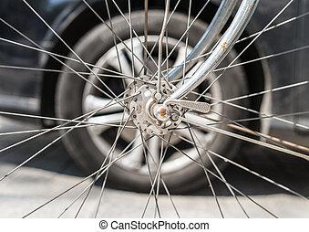 Bicycle versus car. Wheels against each other.