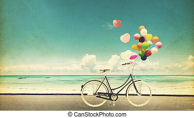 bicycle vintage with heart balloon on beach blue sky