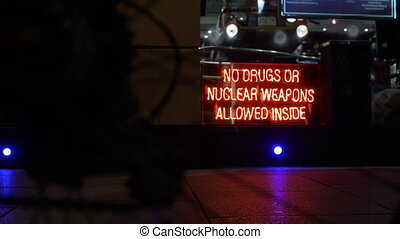 "A bicycle in foreground, then focus to the back of a neon lit sign ""No drugs or nuclear weapons allowed inside"""