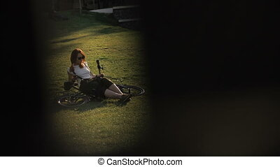 Bicycle woman cyclist with mobile phone in hand lying on...