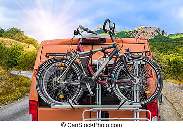 bicycles on the trunk of a minivan moving on a mountain road