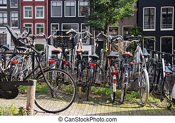 Bicycles parked on a bridge in Amsterdam, The Netherlands. A lot of parked bikes on the pavement