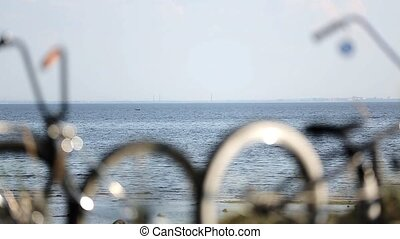 Bicycles stay on hill focus in out, calm sea on background ....