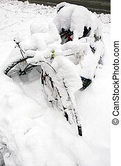 Bicycles under snow - Two bicycles parked on the side of a...