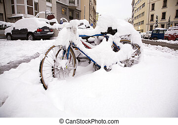 Bicycles under snow - Bicycles parked on the side of a road...