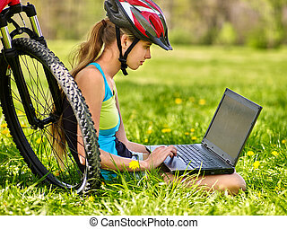 Bicycling girl wearing helmet cycling sitting near bicycle watch laptop.