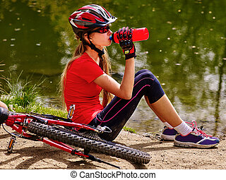 Bicycling girl wearing helmet drinking of bottle water. - ...