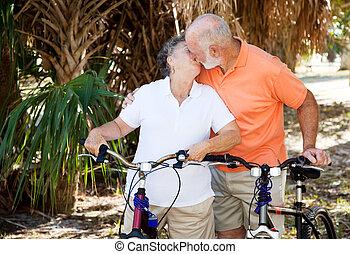 Bicycling Seniors Kiss