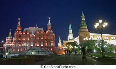 Bicyclist and pedestrians walk by Manezhnaya square near kremlin in Moscow at night