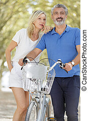 bicyclist couple in pine forest romantic walk