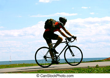 Bicyclist - Man riding a bicycle on sea shore trail, motion ...