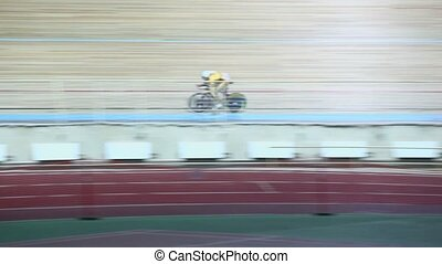 Bicyclist rides by track during race in gymnasium