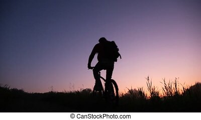 bicyclist rides uphill against sunset sky
